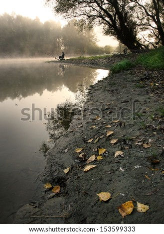 Man angling beside river on foggy morning - stock photo