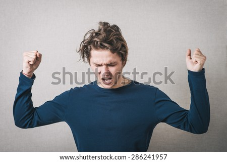 Man angry, shouts, lifting his hands up into fists. Gray background - stock photo