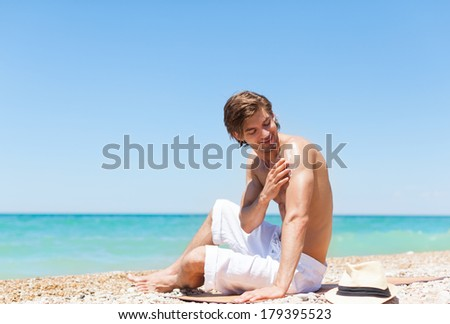 man apply sunscreen protection lotion on back tanned body, sitting on summer beach travel ocean vacation, concept of applying skin care sun protect - stock photo