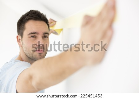Man applying duct tape on wall - stock photo