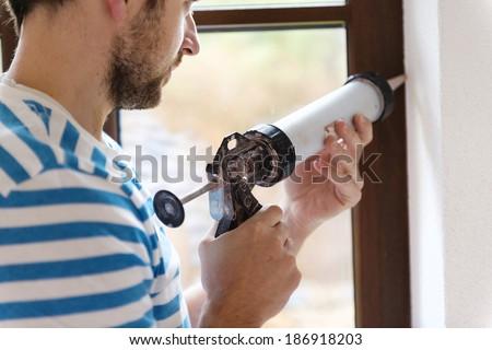 Man applying silicone sealant with caulking gun - stock photo