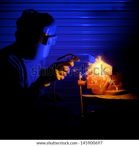 Man arc welding some steel in a workshop - stock photo