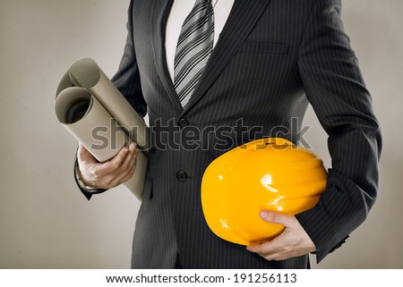 Man architect wearing suit holding blueprint and helmet. Confident construction manager with architectural project papers.  - stock photo