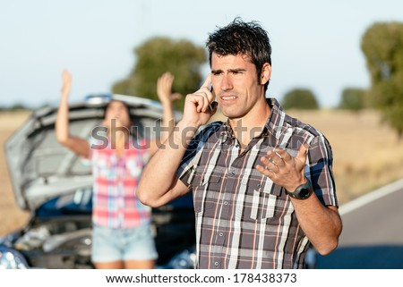 Man arguing on the cellphone with car insurance service. Upset couple in road trip problems because of breakdown engine. - stock photo