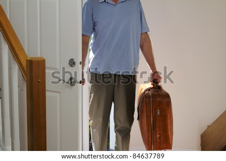 Man arriving from business travel inside the front door of his home. - stock photo