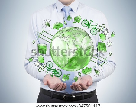 man as if holding a sphere with a green picture of eco energy icons arranged in circle, earth in the centre, concept of clean and safe  environment, breast view - stock photo
