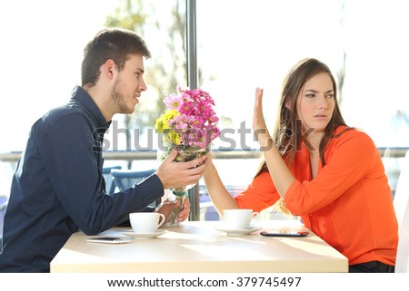 Man asking for forgiveness offering a bunch of flowers to his girlfriend in a coffee shop with an exterior background. Couple problems concept - stock photo