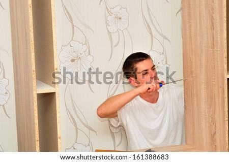 Man assembling a wardrobe at home. - stock photo
