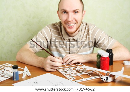 man assembling plastic airplane model and painting pieces, smiling, looking at camera - stock photo