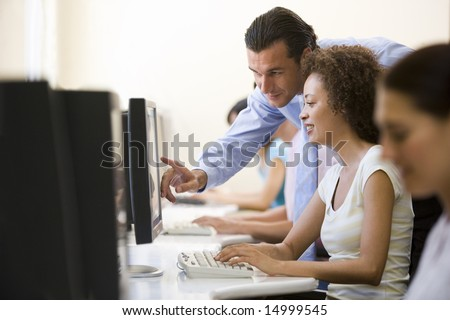 Man assisting woman in computer room - stock photo