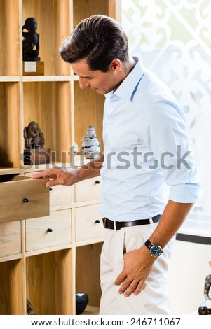 Man at cabinet in furniture store showroom - stock photo