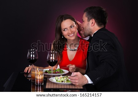 Man At Dining Table Whispering In Woman's Ear - stock photo