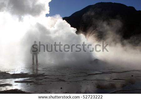 Man at El Tatio geysers, Chile at sunrise - stock photo