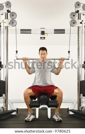 Man at gym lifting weights on weight machine. - stock photo