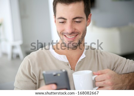 Man at home connected on smartphone - stock photo