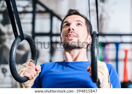 Man at rings doing fitness exercise in gym - stock photo