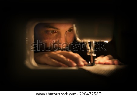 Man at Sewing Machine in a Dimly Lit Room - stock photo