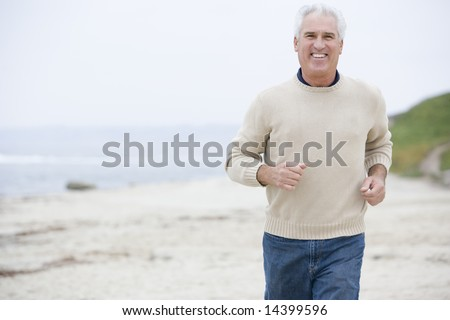 Man at the beach running and smiling - stock photo