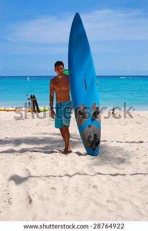 Man at the beach standing next to his surf - stock photo