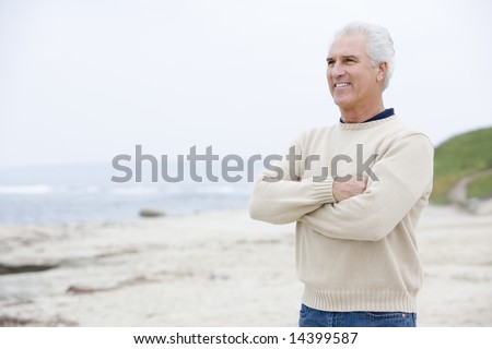 Man at the beach with arms crossed smiling - stock photo