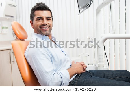 Man at the dentist for dental care - stock photo