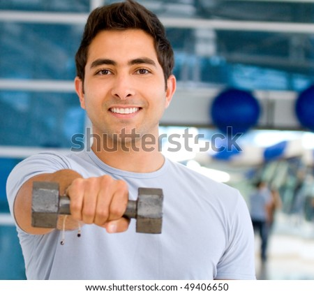 Man at the gym lifting a free-weight and smiling - stock photo