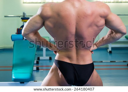 Man at the gym. Man makes exercises. Sport, power, dumbbells, tension, exercise - the concept of a healthy lifestyle. Article about fitness and sports. - stock photo