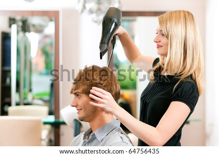 Man at the hairdresser, she has finished the cut and is drying his hair with a blow dryer - stock photo