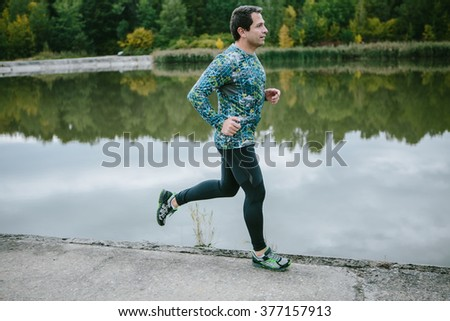 Man at the lake running against green cloudy nature - stock photo