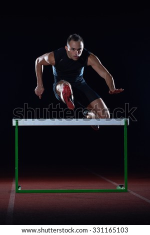 man athlete jumping over a hurdles on athletics race track - stock photo