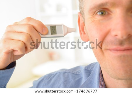 Man attempting to measure body temperature with thermometer in ear - stock photo