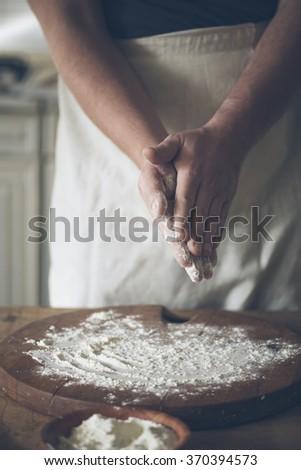 Man baking bread in kitchen. - stock photo