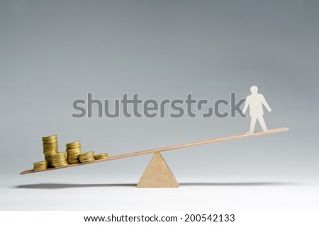 Man balanced on seesaw over a stack of coins - stock photo
