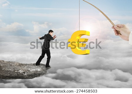 Man balancing on rocky cliff for 3D golden euro symbol bait from fishing rod hand holding, with sunlight sky cloudscape background - stock photo