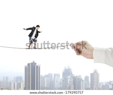 Man balancing on rope with city view - stock photo