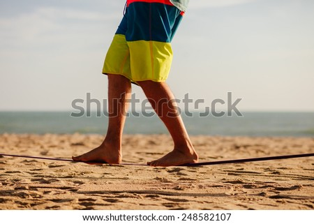 man balancing on slackline with sea view on the beach - stock photo