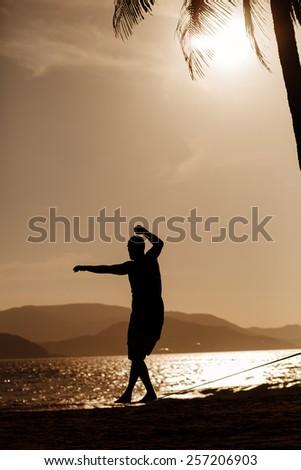 man balancing on slackline with sea view silhouette - stock photo