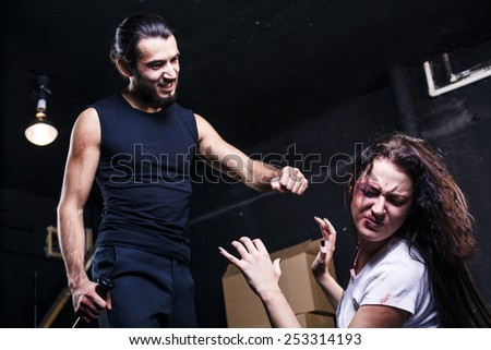 Man beating up his wife on black background - stock photo
