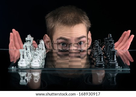 Man behind glass chess pieces on a glass chessboard with a reflection isolated on a black background ready to play a game - stock photo