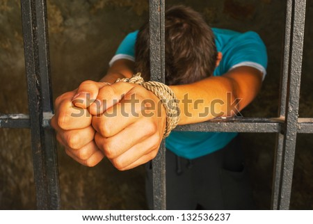 Man behind the bars with hands tied up with rope - stock photo