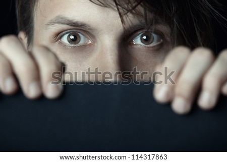 Man behind the black board looking with interest - stock photo