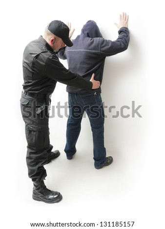 Man being searched by a policeman in black uniform - stock photo