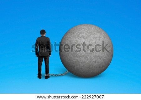 man being trapped with concrete ball isolated on blue - stock photo