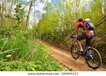 man biking on a countryside road - stock photo