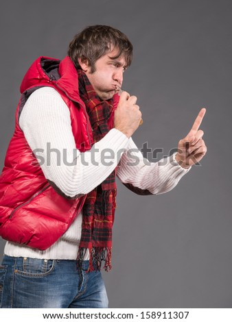 Man blowing a whistle and pointing on a gray background - stock photo