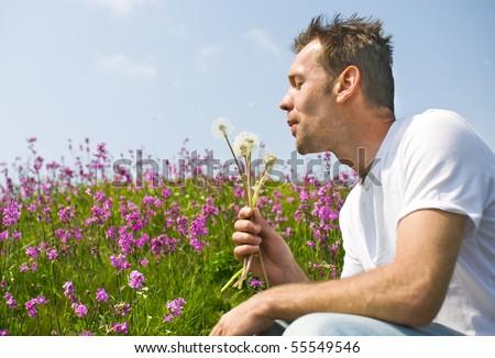 Man blowing dandelions - stock photo