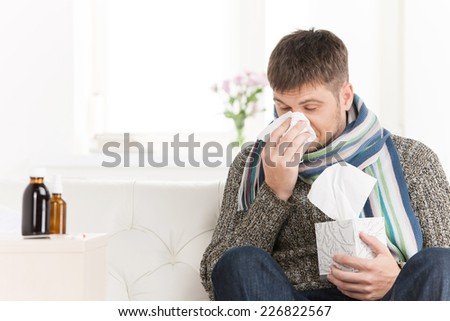 Man blowing his nose in his living room. closeup on guy sitting on sofa and sneezing - stock photo