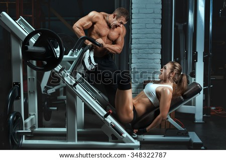Man bodybuilder trains the a woman. Woman on the machine to swing your leg muscles. - stock photo