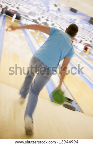 Man bowling, rear view (blurred motion) - stock photo