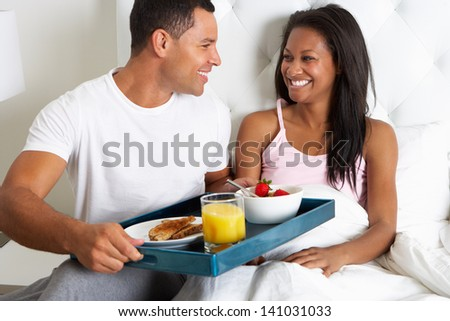 Man Bringing Woman Breakfast In Bed On Tray - stock photo
